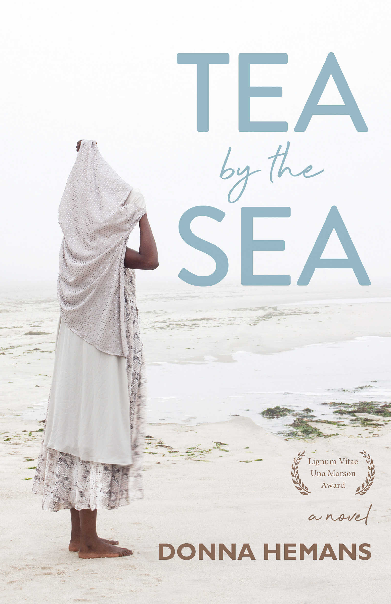 A photograph of a white sand beach with a woman standing on the left covering herself with a large piece of fabric and blue script towards the right that reads Tea by the Sea a Novel by Donna Hemans.