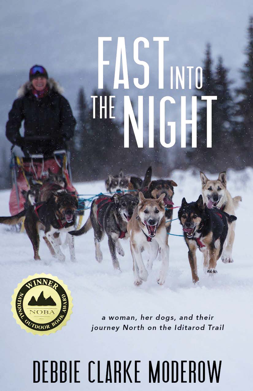 A photograph of a woman in the snow riding a sled being pulled by dogs and white script that reads Fast Into the Night: a woman, her dogs, and their journey North on the Iditarod Trail by Debbie Clarke Moderow.